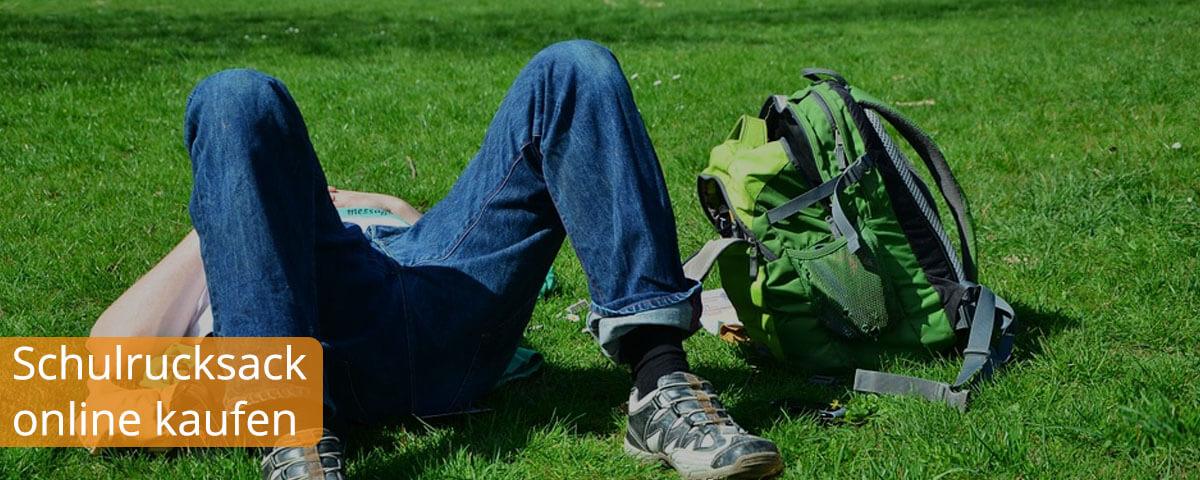 Person liegt neben einem Schulrucksack auf einer Wiese
